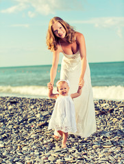 happy family, mother and baby daughter in white dresses on the b