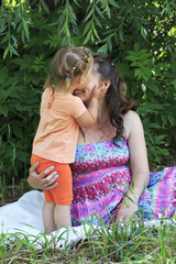 Little girl tenderly kisses and hugs his mother.