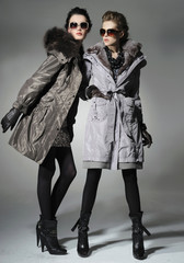 Two Vogue style in coat dresses. Studio portrait