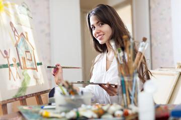 Smiling female artist paints picture
