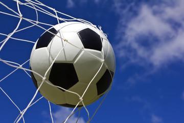 soccer ball in net on blue sky
