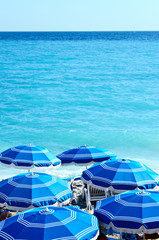sunny blue ocean shoreline in Nice with blue parasols
