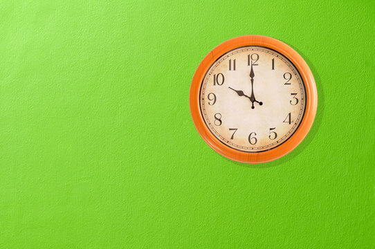 Clock showing 10 o'clock on a green wall