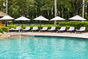 swimming pool with sun beds and white umbrella