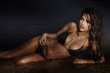 Sensual brunette woman posing on the sea.