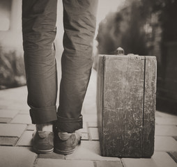 Man with old wooden suitcase, travel concept, retro tinted