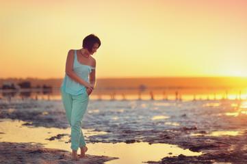 on the beach beautiful girl posing at sunset
