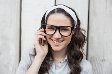 Smiling trendy woman with stylish glasses having phone call