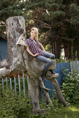 Blonde young country girl sitting on large old stump