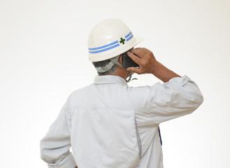 携帯電話で会話をしている作業員