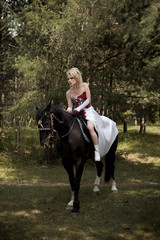 Beautiful young woman with a horse in the forest