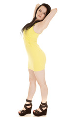 Woman yellow short dress stand hands behind head