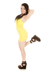 Woman yellow short dress stand one leg up