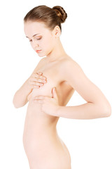 Woman examining her breast for lumps or signs of breast cancer