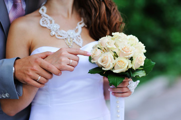 Groom and bride holding hands with wedding rings