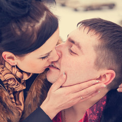 young couple kissing in the winter forest