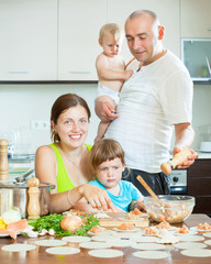 family of four making small dumplings with fish (dumplings) in a