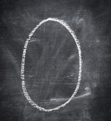 O - letter written on black chalkboard.