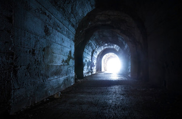Door stickers Tunnel Blue glowing exit from dark abandoned tunnel