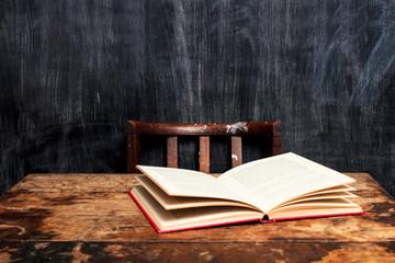 Open book on desk by blackboard