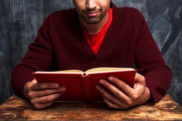 Man reading in front of blackboard