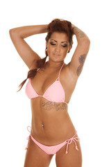 Woman pink bikini tattoos arms in hair