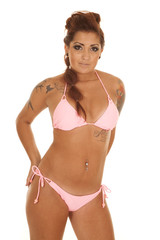 Woman pink bikini tattoos hands on hips