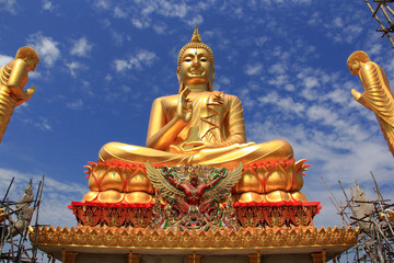Big golden Buddha statue on blue sky