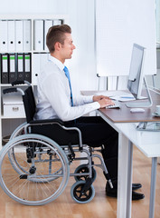 Businessman Sitting On Wheelchair And Using Computer