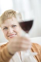 Smiling Woman Holding Up Red Wineglass