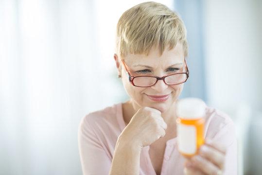 Woman Reading Label On Pill Bottle