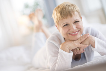 Happy Woman Resting Chin On Hands While Lying In Bed