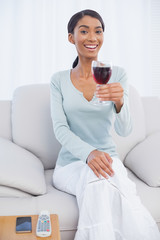 Smiling attractive woman holding glass of red wine