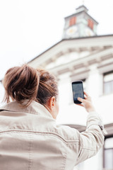 Woman sightseeing and taking photos with phone