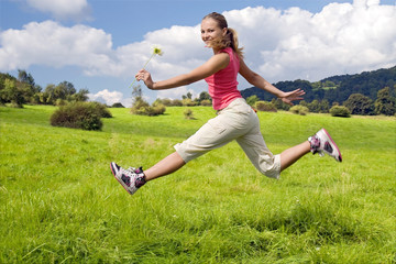 beautiful girl with flower jump on meadow.