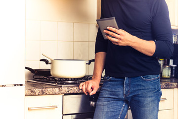 Man with digital reader in kitchen