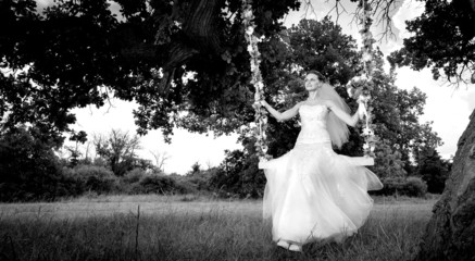 Bride on swing on green glade