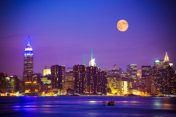 New York City skyline at night under a full moon