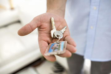 A man holds in his hand the keys of his house, indoor.