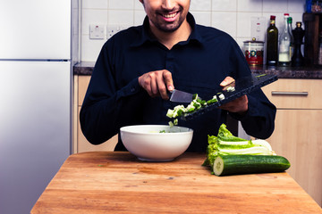 Happy man mixing a salad in kitchen