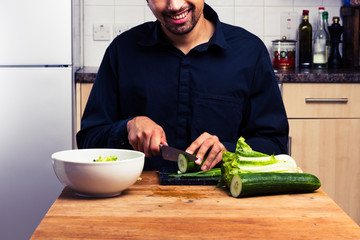 Happy young man making a salad