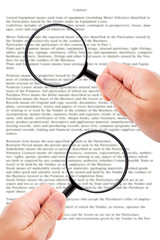 Hands holding magnifying glass reading document