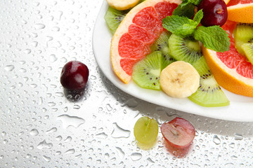 Assortment of sliced fruits on plate with drops