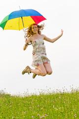 Junge Frau springt mit einem bunten Regenschirm