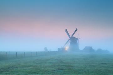 Wall Mural - windmill in fog at sunrise