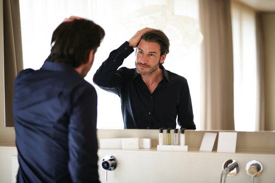 Mann begutachtet sich im Spiegel