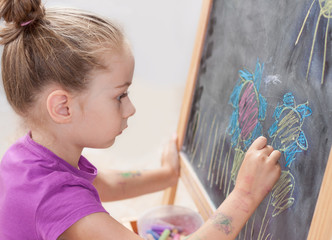 Young girl drawing a picture with a chalk on blackboard