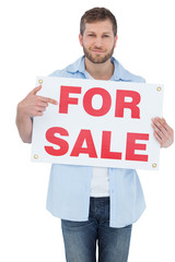 Trendy model holding a for sale sign
