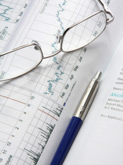 Financial charts, a pen and glasses