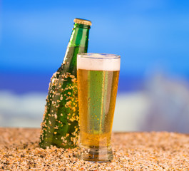 Ice cold green unlabelled bottle of beer in the beach concept